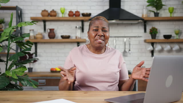 Mature woman in pink t-shirt sits at wooden table and talks