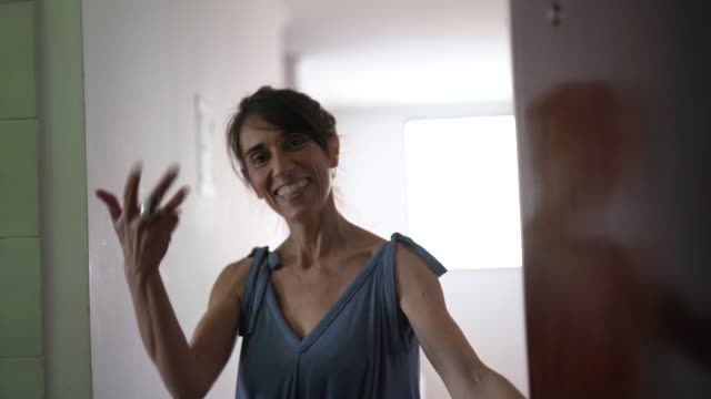 mogen kvinna inbjudan / välkommen gäst hemma - ytterdörr bildbanksvideor och videomaterial från bakom kulisserna