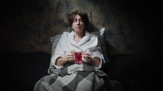Mature woman is drinking herbal tea before sleep