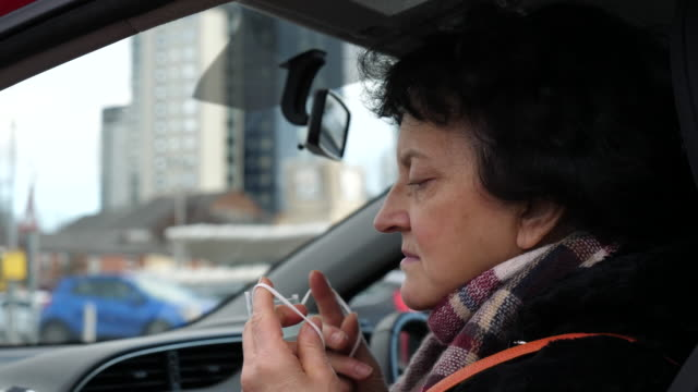 Bидео Mature woman is putting surgical mask on her face in a car