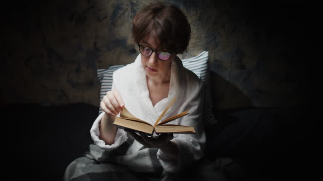 Mature woman is reading a paper book before sleep
