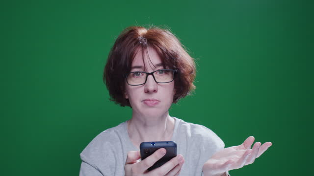 Mature woman is searching information in her smartphone and cannot find it video