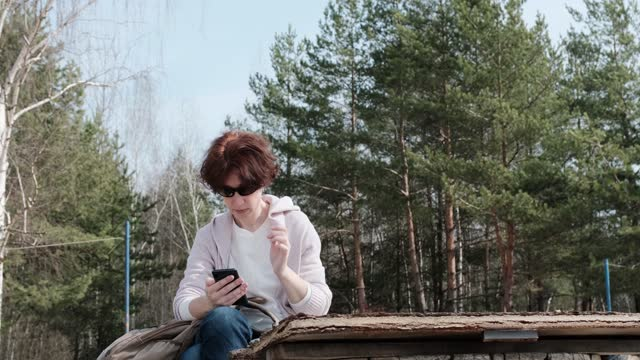 Mature woman is sitting in sunny forest and using smart phone video