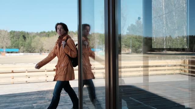 Mature woman is walking along the glass pavilion in public park video