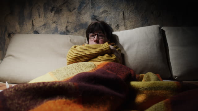 Mature woman is wrapping herself with shawl and blanket while getting fever on the sofa