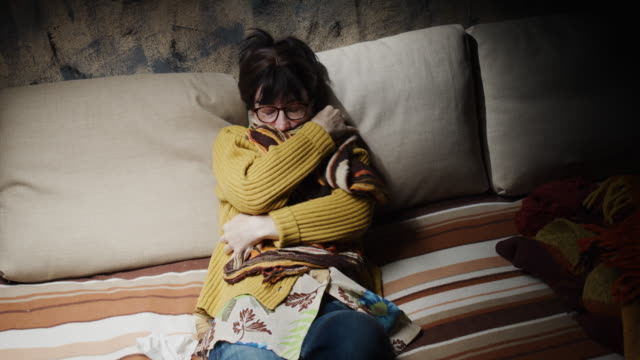 Mature woman is wrapping herself with shawl while getting fever on the sofa