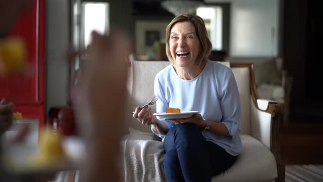 mature woman laughing during family coffee break - family home video stock e b–roll