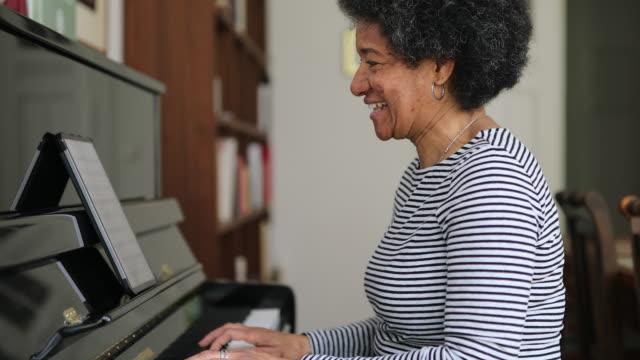 Mature woman learning piano at home during corona virus lockdown