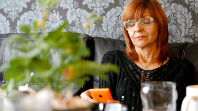 Mature woman looking at her smart phone video