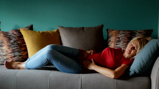 Reife Frau auf dem Sofa liegend und Becken-Schmerz zu spüren – Video