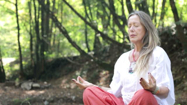 donna matura che medita nella natura - hippy video stock e b–roll