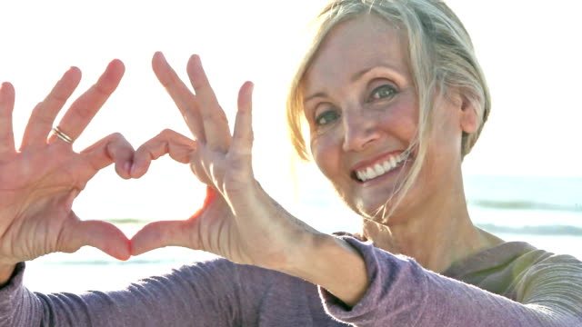 Mature woman on sunny beach makes heart shape with hands video