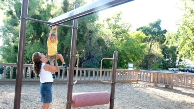 mature woman playing with her son at the park - pantaloncini video stock e b–roll