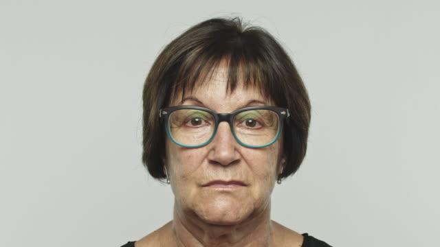 mature woman portrait looking at camera - serio video stock e b–roll