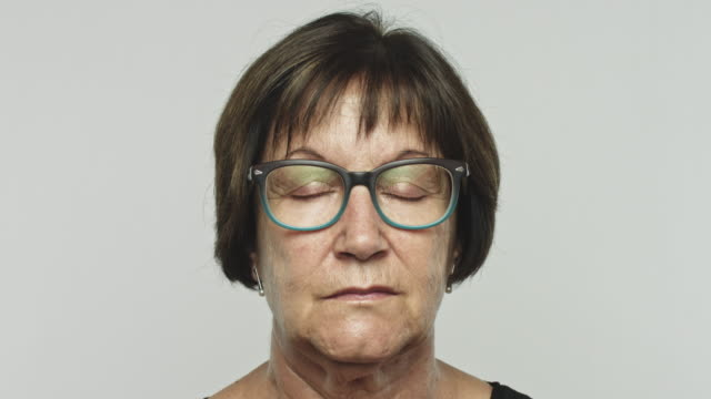 Mature woman portrait with eyes closed Video portrait of caucasian mature woman opening eyes with relaxed expression against gray background. Real woman with closed eyes and eyeglasses. Studio 4K RAW video with sharp focus on eyes. eyes closed stock videos & royalty-free footage