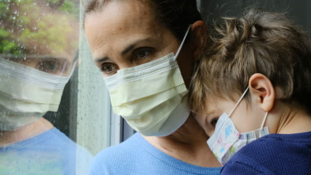 mature woman posing with her son, both with protective masks, very sad looking through window worried about covid-19 lockdown - lockdown filmów i materiałów b-roll