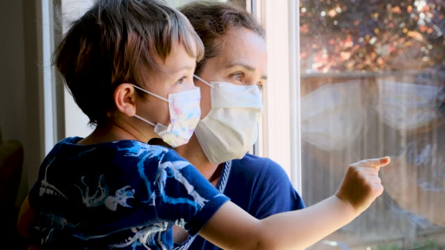 mature woman posing with her son, both with protective masks, very sad looking through window worried about covid-19 lockdown - parenting stock videos & royalty-free footage