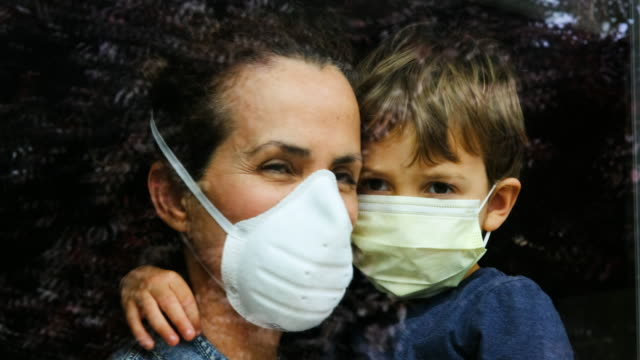 Mature woman posing with her son, both with protective masks, very sad looking through window worried about Covid-19 lockdown