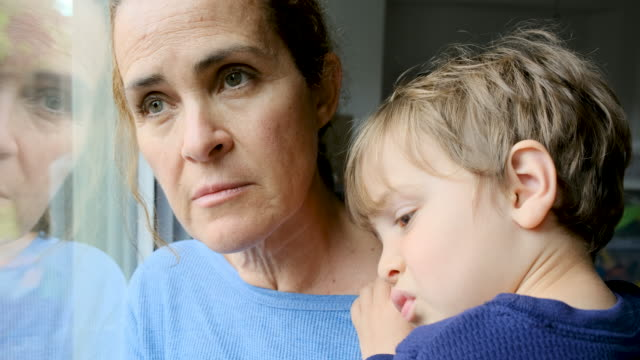 Mature woman posing with her son, very sad looking through window worried about Covid-19 lockdown