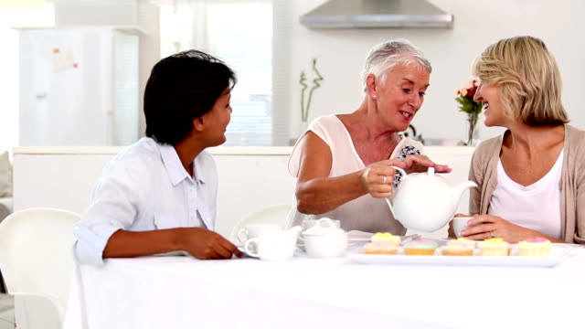 Mature woman pouring tea to her friends cup video