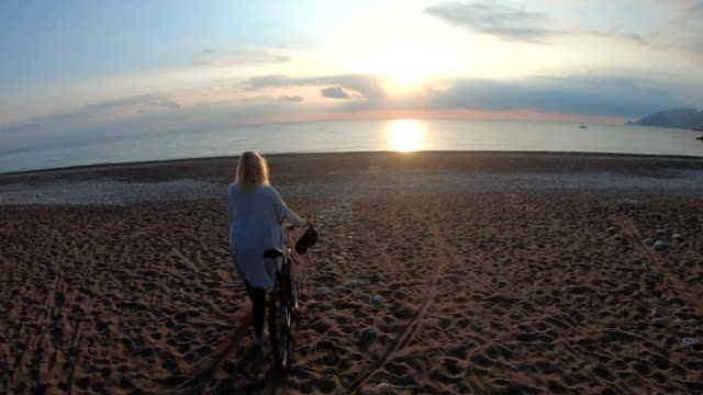 vídeos de stock, filmes e b-roll de a mulher madura empurra a bicicleta através da praia no nascer do sol - férias na praia