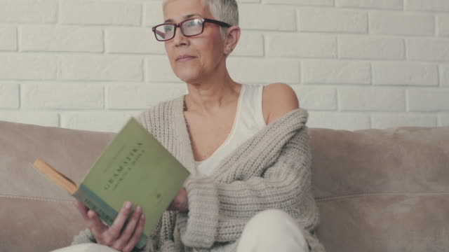 Mature woman reading a novel while relaxing on the sofa. video