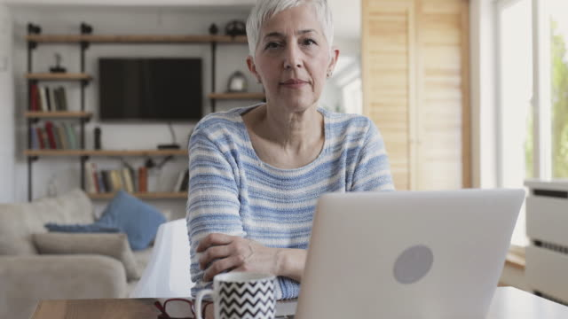 Mature woman reading something from the Internet on her laptop at home. video
