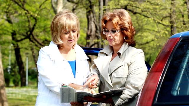 stockvideo's en b-roll-footage met mature woman reading the road map. - roadmap