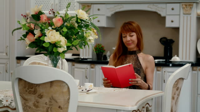 Mature woman reads book sitting at kitchen table video