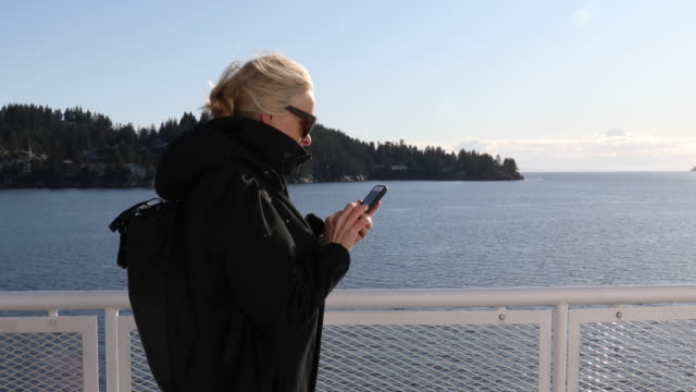 Mature woman relaxes on deck on ferry boat