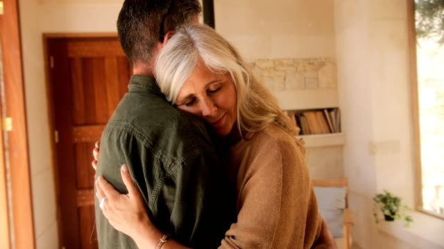 Mature woman relaxing in romantic husband's arms at home