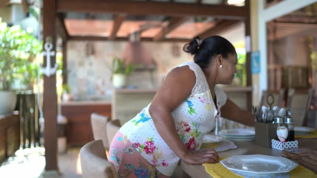 Mature woman setting the table for lunch at home
