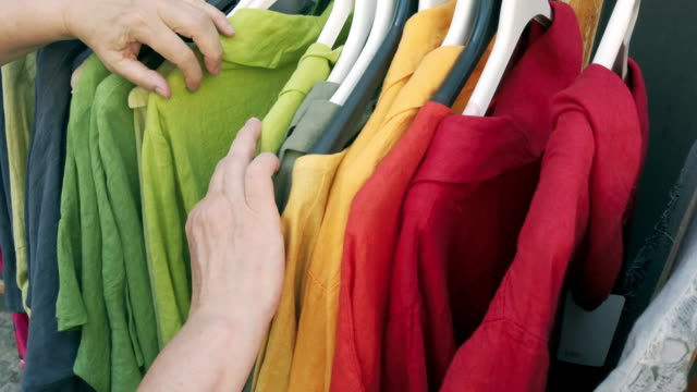 Mature Woman Shopping for Clothing Handheld close-up shot made in 4K/Ultra High Definition rack stock videos & royalty-free footage