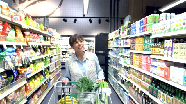 Mature woman shopping for groceries walking down aisle A woman in the supermarket buying groceries, pushing a shopping cart down an aisle of the store, looking around. She is a mature mixed race Caucasian and Asian woman in her 40s wearing casual clothing. woman pushing cart stock videos & royalty-free footage