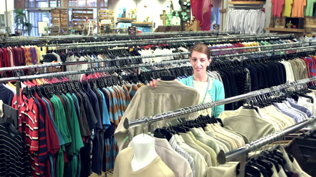 Mature woman shopping for men's shirts in clothing store video