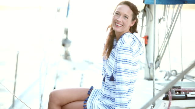 Mature woman sitting on deck of sailboat video