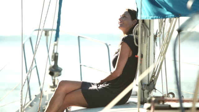 Mature woman sitting on deck of sailboat A mature woman in her 40s smiling, relaxed, looking up and enjoying the view as she sits on the deck of a luxury sailboat. cross legged stock videos & royalty-free footage