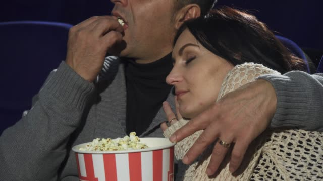 Mature woman sleeping on the shoulder of her husband at the cinema video