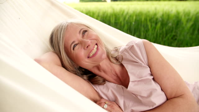 Mature woman smiling happily in a hammock outdoors video