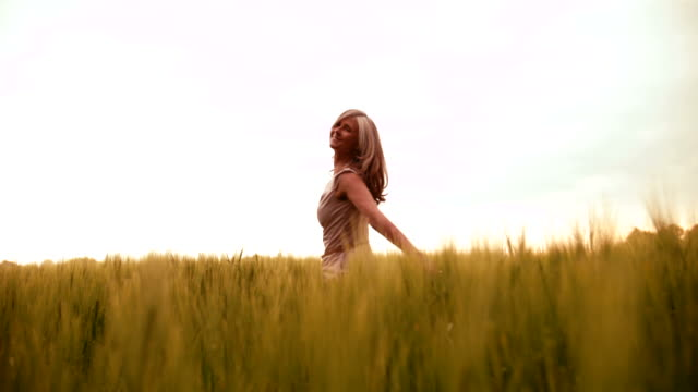 Mature woman spinning happily in wheat field video
