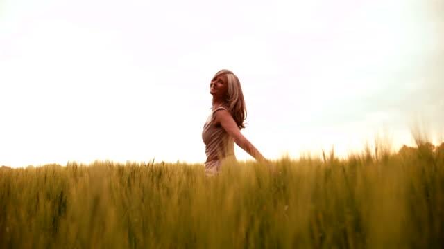 mogen kvinna snurrar glatt i vetefält - glädje bildbanksvideor och videomaterial från bakom kulisserna