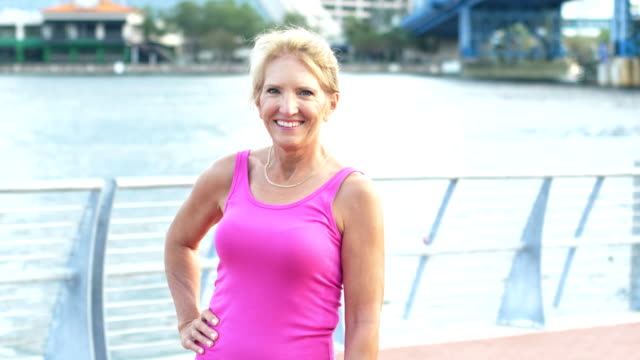 Mature woman standing on waterfront A mature woman in her 50s standing on a city waterfront, wearing a pink shirt. She is smiling at the camera with her hand on her hip. tank top stock videos & royalty-free footage