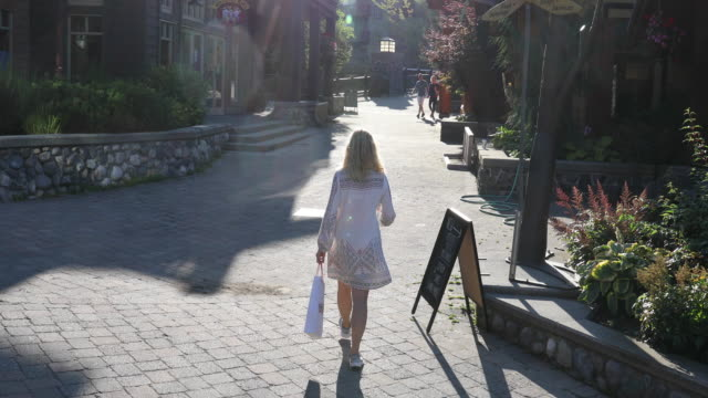Mature woman strolls village streets, with shopping bag