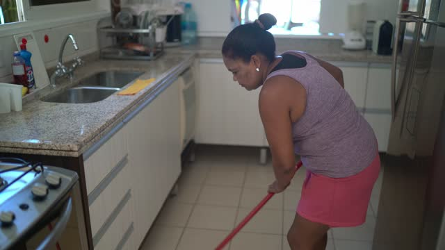 Mature woman sweeping floor at home