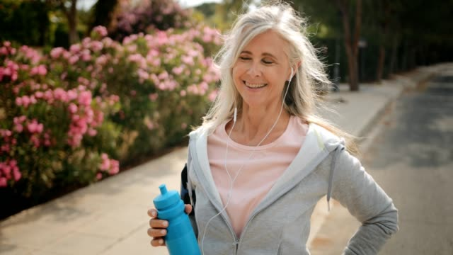 Mature woman taking a break from running outdoors and drinking water Happy senior woman with smartwatch listening to music and drinking water after working out outdoors healthy lifestyle stock videos & royalty-free footage