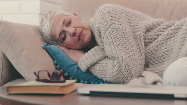 mature woman taking a nap on the sofa while resting at home. - sonnecchiare video stock e b–roll