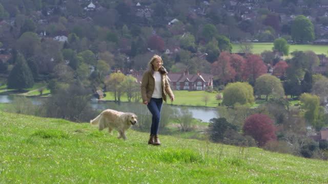 reife frau mit hund für spaziergang in landschaft geschossen auf r3d - hundesitter stock-videos und b-roll-filmmaterial