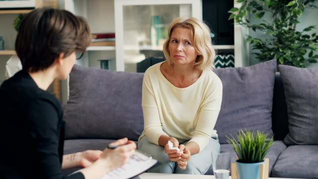 Mature woman talking to female psychologist sitting on couch in modern office Attractive mature woman is talking to female psychologist sitting on comfy couch in modern office holding paper tissue. People, psychology and workplace concept. psychiatrist stock videos & royalty-free footage