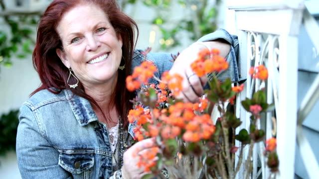 Mujer madura tiende a flores fuera de su casa - vídeo