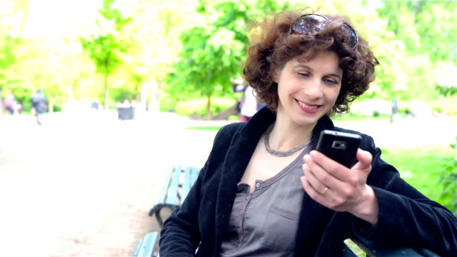 DOLLY: Mature woman texting in a park video